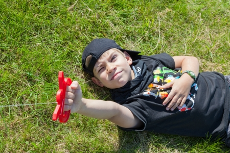 The boy lies on meadow and holding kite  Raffish face  Happiness  Stock Photo