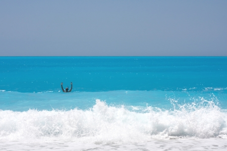 Lone snurking man on the big waves. White and blue.