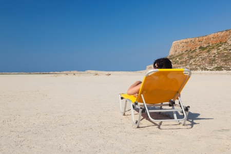 Lonely woman on an empty beach  White sand  Blue sky  Nobody  Free space  Orange chaise  Stock Photo