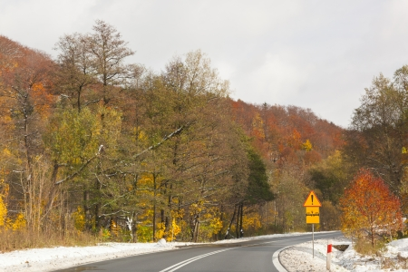 Road on the mountains. Autumn. Colored trees. Sign. Snow.