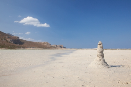 Small tower of white sand. Beach. Blue sky. Nobody. Free space.