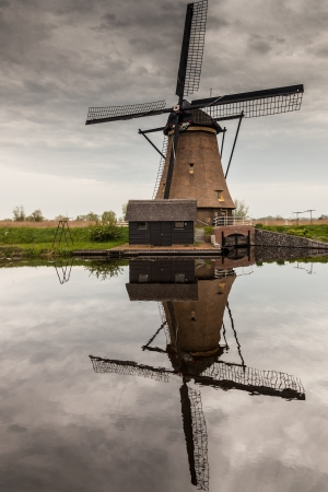 Dutch windmill. Reflection on water. River and gray sky. Stock Photo