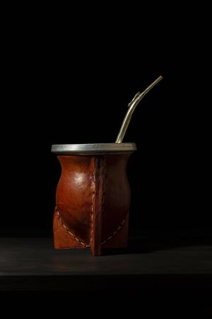 Traditional Argentine mate made in pumpkin covered in leather with a silver straw on a black background