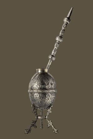 Ancient Argentine mate in silver worked in relief with straw on a brown background Reklamní fotografie