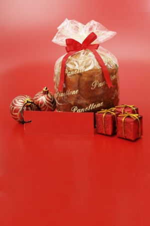 Panettone on red background with xmas ornaments photo