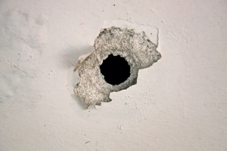 Bullet hole on the white wall