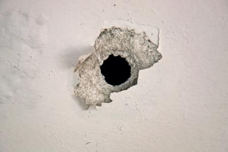 Kogelgat op de witte muur