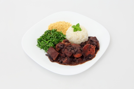 Brazilian Feijoada on a plate for lunch or dinner  Dish on a white background  Stock Photo