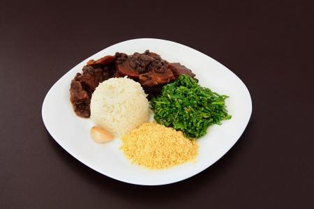 Brazilian Feijoada on a plate on brown leather background  Standard-Bild