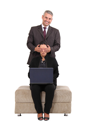 Brazilian business man covering eyes of a brazilian business woman co-worker isolated on white .