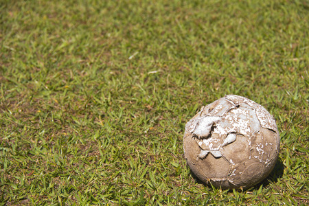durable: A very used soccer ball on grass. What a durable item, but it is time for a new one.