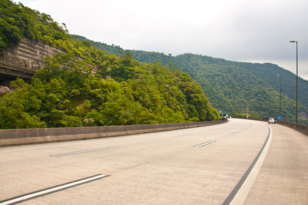 berm: Going to litoral through the Imigrantes highway in a cloudy day. Stock Photo