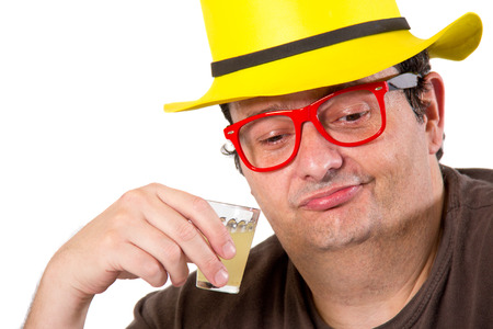 man 40 50: Close up of a Brazilian thoughtful guy drinking a sugar cane brandy on white background