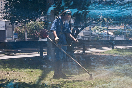 safety net: Sao Paulo, SP, Brazil - Dec 06, 2008. City care. A worker mowing laws behind a safety net on a avenue in Sao Paulo city. Editorial