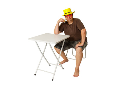 boozer: Brazilian man sat on a pub table drinking a lemon brandy isolated on white background.