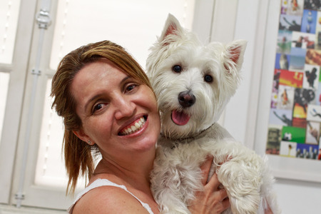 westie: Happy Brazilian woman owner of her West Higland White Terrier dog.