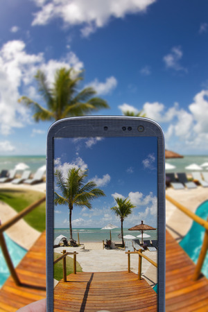 accessing: Smatrphone and a landscape. Idea of taking shots accessing apps Internet blogs and others. The blur image is a sunny day at Arraial dAjuda Eco Resort in Bahia  Brazil.