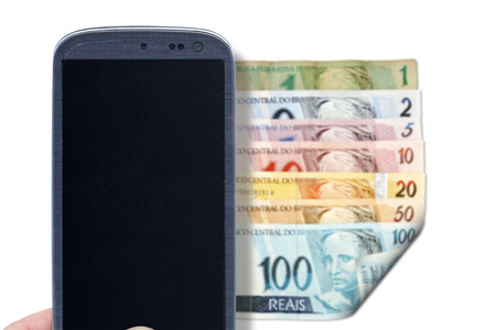 downpayment: Smatrphone and brazilian money. Idea for comparing prices apps financial apps scanning money apps accessing apps Internet blogs and others. The blur image are Reais Real front of Brazilian money. From one to hundred reais.