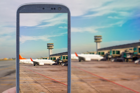 accessing: Smatrphone and airport background. Idea of taking shots accessing apps Internet blogs and others. The blur image is an airport scene with airplane landed and another taxing for taking off. Stock Photo