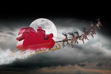 santa clos: Pap� Noel que monta un trineo conducido por renos en una noche nublada Foto de archivo