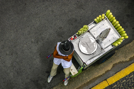 VENDEDOR: Top view of a street seller which sells corn on the cob on streets