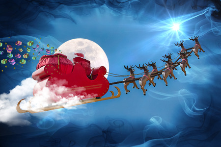 Santa Claus riding a sleigh led by reindeers delivering gifts Stock Photo
