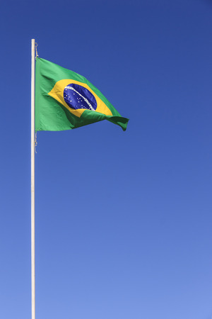 patriot: Brazilian flag waving on top of a flagpole in a clear sky day