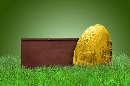 golden background: Chocolate bar and golden Easter egg on grass on green background