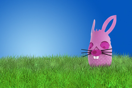 blue green background: Funny pink Easter bunny on grass on blue background Stock Photo