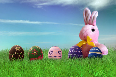 green background: Painted Easter eggs and pink bunny on grass on sky background