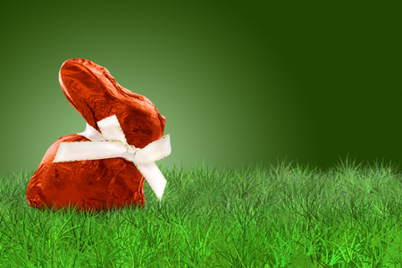 green background: Wrapped Easter bunny with red aluminium on grass on grass on green background