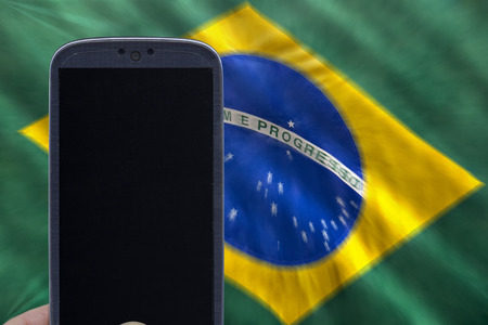 Holding smartphone with brazilian flag on the background