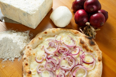 Typical Italian Pizza cooked in electric oven with ingredients in the background on a wood table Stock Photo - 17870372