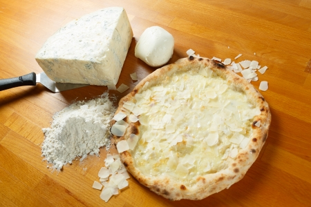 Typical Italian Pizza cooked in electric oven with ingredients in the background on a wood table Stock Photo - 17870304