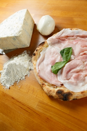 Typical Italian Pizza cooked in electric oven with ingredients in the background on a wood table Stock Photo - 17870290