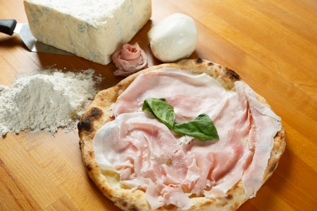 Typical Italian Pizza cooked in electric oven with ingredients in the background on a wood table Stock Photo - 17870465