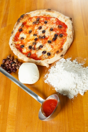 Typical Italian Pizza cooked in electric oven with ingredients in the background on a wood table Stock Photo - 17870239