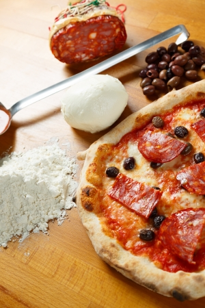 Typical Italian Pizza cooked in electric oven with ingredients in the background on a wood table Stock Photo - 17870241