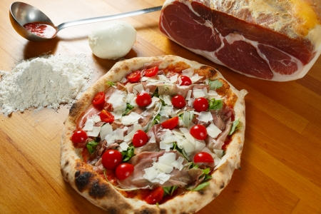 Typical Italian Pizza cooked in electric oven with ingredients in the background on a wood table Stock Photo - 17870148