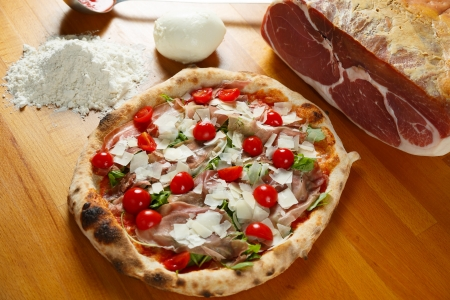 Typical Italian Pizza cooked in electric oven with ingredients in the background on a wood table Stock Photo - 17870104
