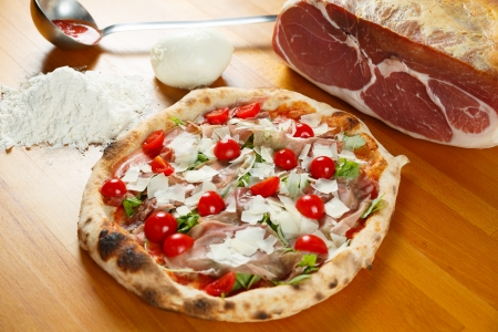 Typical Italian Pizza cooked in electric oven with ingredients in the background on a wood table Stock Photo - 17870484