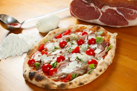 Typical Italian Pizza cooked in electric oven with ingredients in the background on a wood table Stock Photo - 17871076