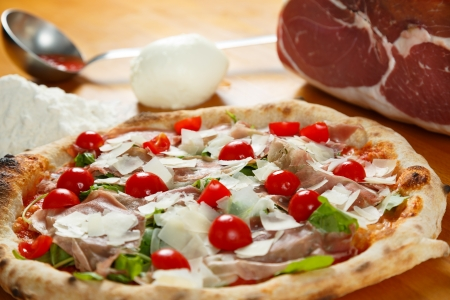 Typical Italian Pizza cooked in electric oven with ingredients in the background on a wood table Stock Photo - 17870646