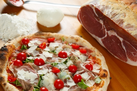 Typical Italian Pizza cooked in electric oven with ingredients in the background on a wood table Stock Photo - 17871145