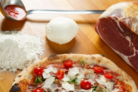 Typical Italian Pizza cooked in electric oven with ingredients in the background on a wood table Stock Photo - 17871279