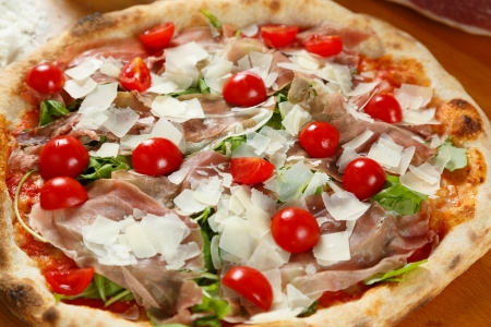 Typical Italian Pizza cooked in electric oven with ingredients in the background on a wood table Stock Photo - 17871135