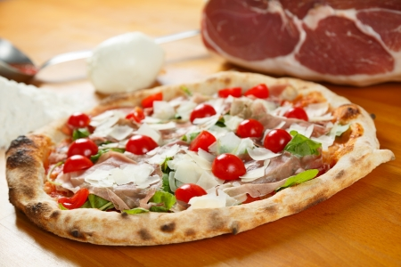Typical Italian Pizza cooked in electric oven with ingredients in the background on a wood table Stock Photo - 17870838