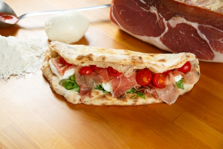 Typical Italian Pizza cooked in electric oven with ingredients in the background on a wood table Stock Photo - 17870979