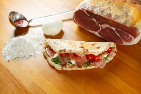 Typical Italian Pizza cooked in electric oven with ingredients in the background on a wood table Stock Photo - 17870076