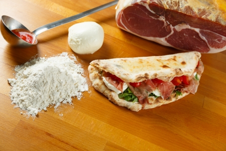 Typical Italian Pizza cooked in electric oven with ingredients in the background on a wood table Stock Photo - 17870136